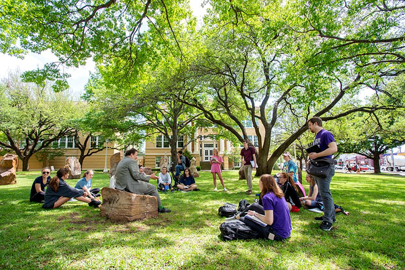A professor teaching students in an outdoor space
